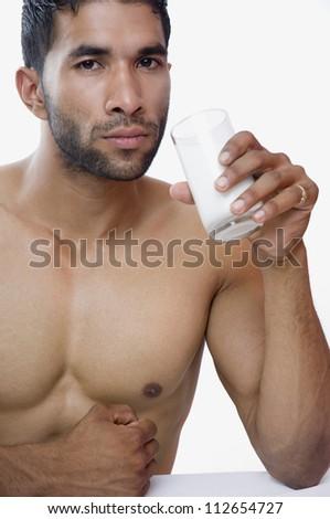Portrait of a macho man drinking milk - stock photo