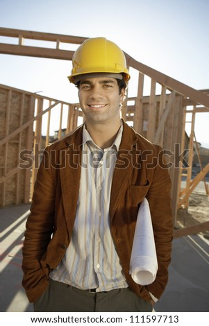 Portrait of a male architect standing with hands in pockets at construction site - stock photo