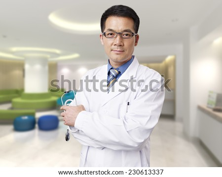 portrait of a male asian doctor in hospital lobby. - stock photo