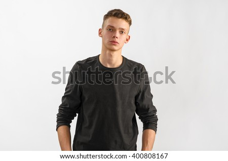 portrait of a male caucasian teenager on gray background - stock photo