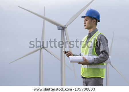 Portrait of a male Chinese industrial engineer at work checking winturbines. - stock photo