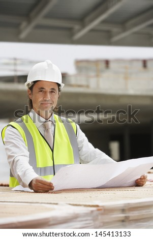 Portrait of a male construction worker with blueprint at site - stock photo