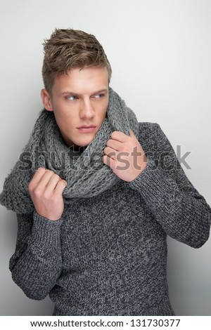 Portrait of a male fashion model holding winter scarf - stock photo