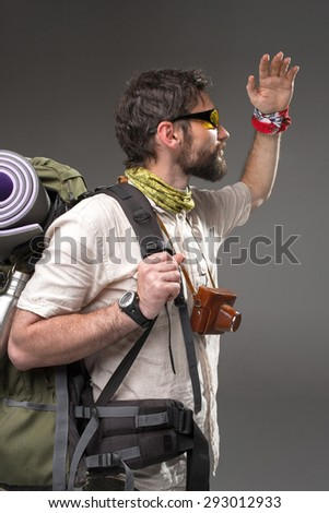 Portrait of a male fully equipped tourist with backpack and the camera on gray background. side view. tourist looking into the distance - stock photo