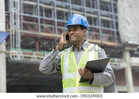 Portrait of a male Indian builder or industrial engineer at work using phone. - stock photo