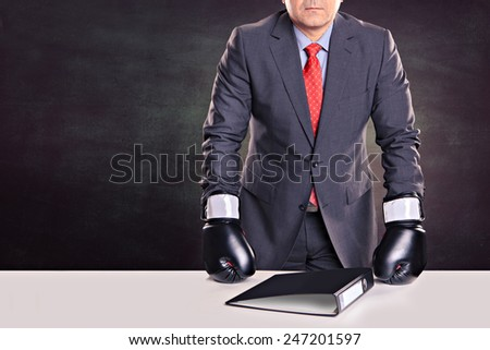 portrait of a male office worker with boxing gloves in the defensive stance - stock photo