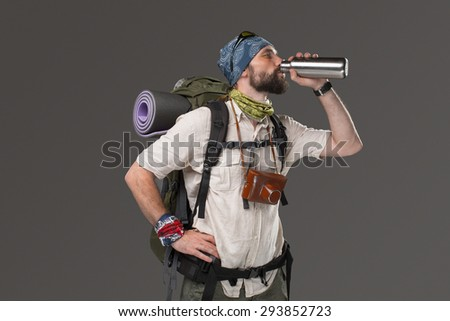 Portrait of a male smiling fully equipped tourist with backpack and the camera on gray background. tourist drinking tea at rest - stock photo