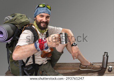 Portrait of a male smiling fully equipped tourist with backpack and the camera sitting on gray background. tourist drinking tea at rest - stock photo