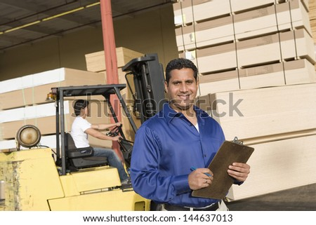 Portrait of a male supervisor with clipboard and forklift truck driver in the background - stock photo