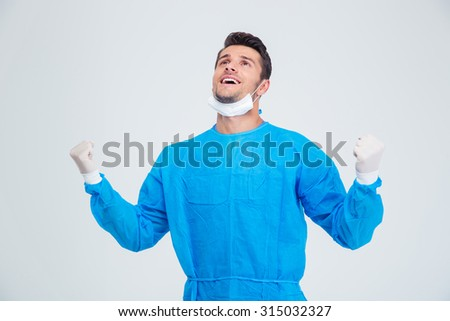 Portrait of a male surgeon celebrating his success isolated on a white background - stock photo