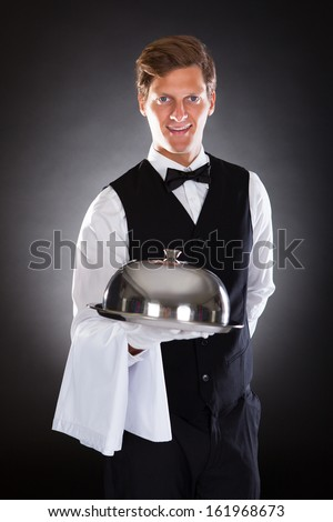 Portrait Of A Male Waiter Holding Tray And Lid Over Black Background - stock photo