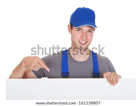 Portrait Of A Male Worker Holding Blank Placard On White Background - stock photo