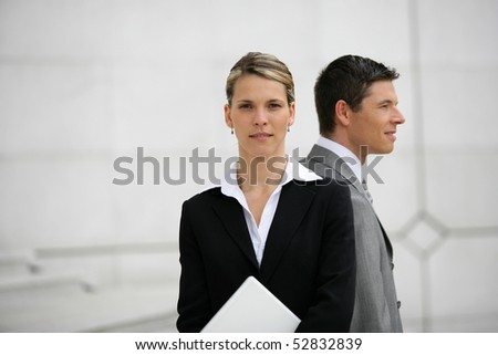 Portrait of a man and a woman holding a laptop computer - stock photo