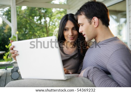 Portrait of a man and woman sitting on a sofa with a laptop computer - stock photo