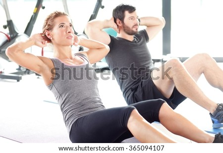 Portrait of a man and woman training together at the gym. Personal trainers doing sit-ups at fitness room. - stock photo
