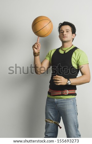 Portrait of a man balancing a basketball on fingertip - stock photo