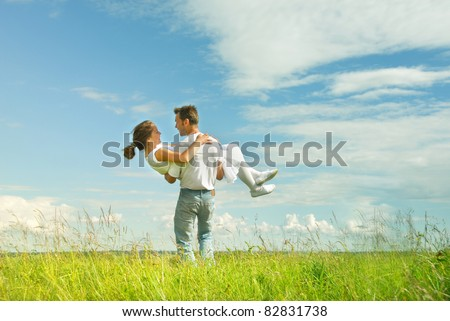 Portrait of a  man carrying a woman in his arms - stock photo