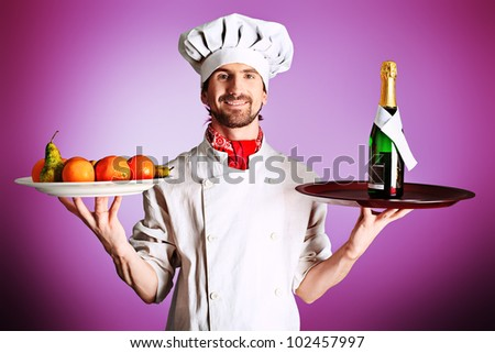 Portrait of a man cook holding a bottle of champagne and fruits. Shot in a studio. - stock photo