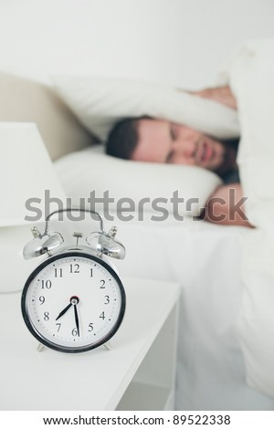 Portrait of a man covering his ears with a pillow while his alarm clock is ringing - stock photo