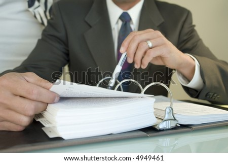 Portrait of a man dressed in business attire reading some paperwork in a binder - stock photo