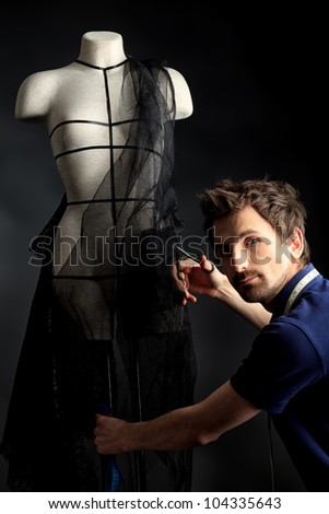 Portrait of a man fashion designer working with dummy at studio. - stock photo