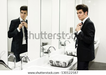 Portrait of a man getting dressed in a public restroom with mirror - stock photo