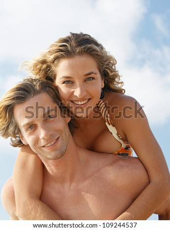 Portrait of a man having fun with his girlfriend while being playful on the beach. - stock photo