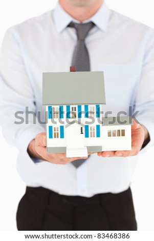 Portrait of a man holding a miniature house against a white background - stock photo