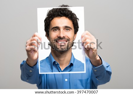 Portrait of a man holding a smiling image of himself - stock photo
