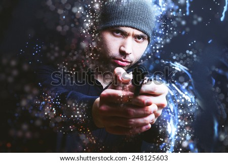 Portrait of a man holding gun against a black background - stock photo