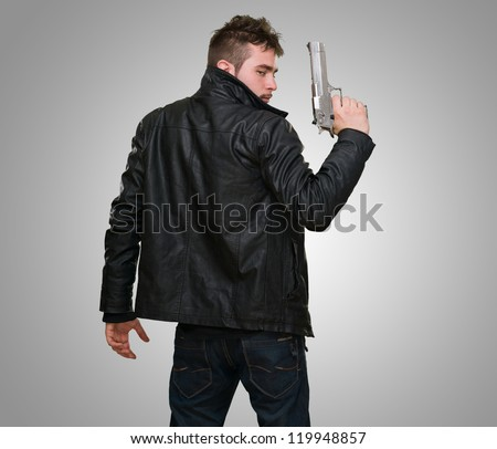 Portrait Of A Man Holding Gun against a grey background - stock photo