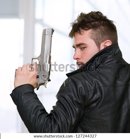 Portrait Of A Man Holding Gun against an abstract background - stock photo