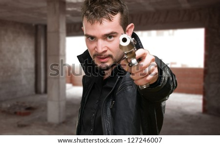 Portrait Of A Man Holding Gun, indoor - stock photo