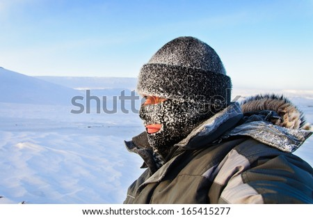 Portrait of a man in a cap and a ski mask. Winter in frost. - stock photo