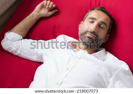Portrait of a man in a white shirt lying on a red pillow and sleeping - stock photo