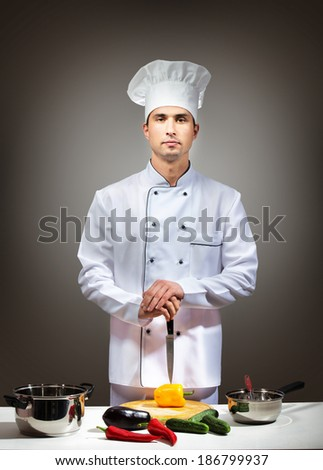 Portrait of a man in chefwear in a kitchen looking at camera - stock photo