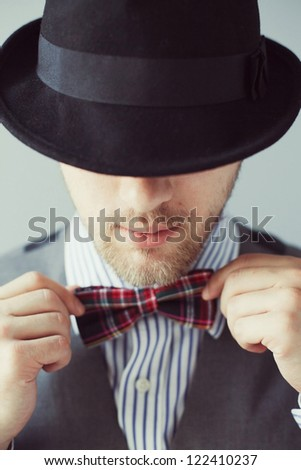 Portrait of a man in the black hat correcting bowtie - stock photo