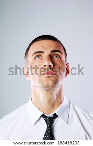 Portrait of a man looking up at copyspace over gray background - stock photo