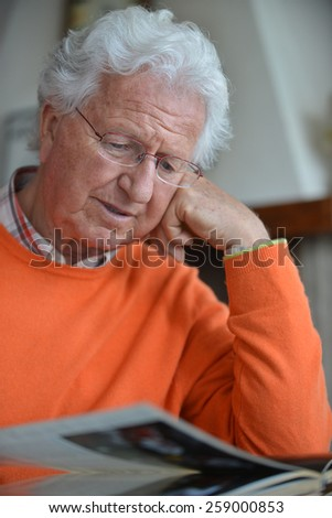 Portrait of a man reading a book in his house - stock photo