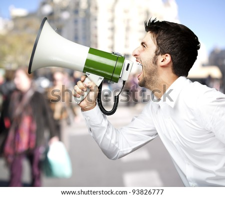 portrait of a man shouting with a megaphone against a street background - stock photo