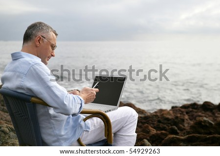 Portrait of a man sitting with a laptop computer face to the sea - stock photo