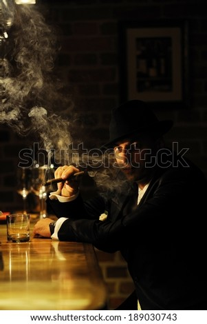 Portrait of a man smoking cigar by the bar. Mafia, retro or gangster style.  - stock photo