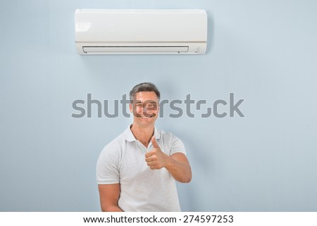 Portrait Of A Man Standing Under Air Conditioner Showing Thumb-up Sign - stock photo