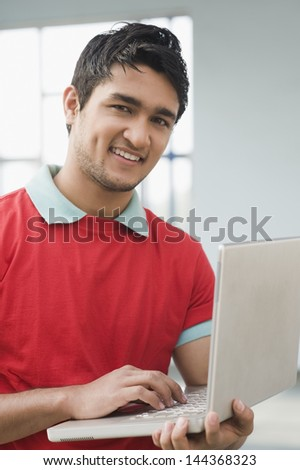 Portrait of a man using a laptop - stock photo