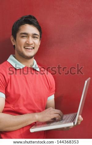 Portrait of a man using a laptop - stock photo