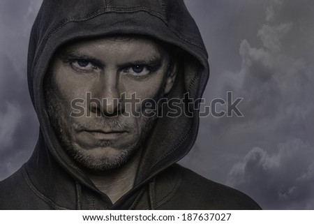 Portrait of a man wearing a hoodie with a strong, intimidating, defiant expression.  - stock photo