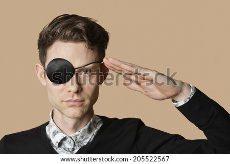 Portrait of a man wearing eye patch saluting over colored background - stock photo