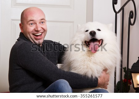 Portrait of a man who is sitting on the porch with his dog. Friendship, four-legged friend. Winter, studio - stock photo
