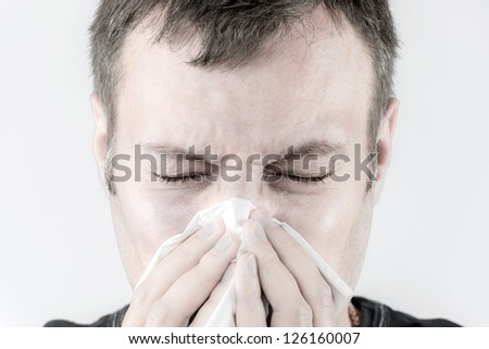 Portrait of a man who is sneezing in a tissue - stock photo