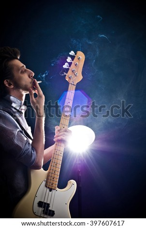 portrait of a man with a guitar and a cigarette on a dark background and a light blue shirt - stock photo